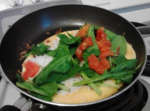 My omelette right before I folded it. The pepperoni is in the eggs and on top I put cheese, spinach and tomato.