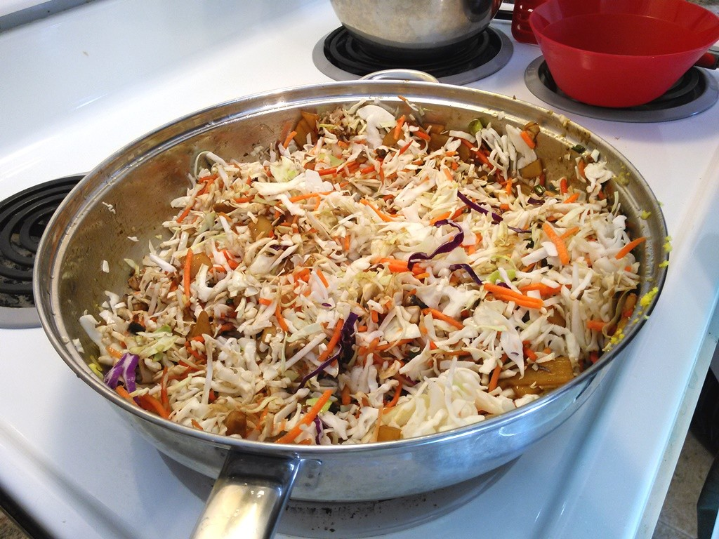 Add the coleslaw mix and cover to steam cook the veggies until the cabbage is slightly wilted.