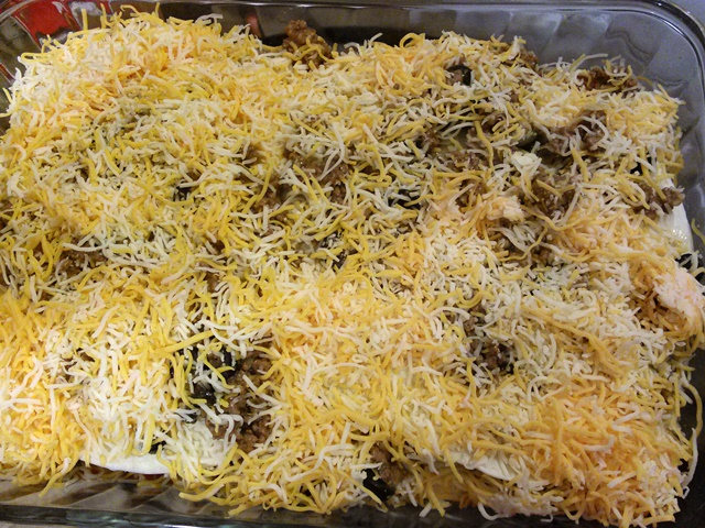 I'm covering several steps with this picture. Cover the second layer of meat with two more tortillas then sprinkle the remaining meat mixture on top of that. finally, sprinkle the remaining 2 cups of shredded cheese evenly over the entire dish.