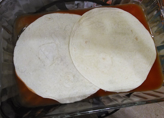 Place two tortillas along the bottom of your dish. They will overlap. If you make a bigger recipe or use a bigger dish than this for some reason, you might need to tear an extra tortilla in half to make sure the bottom is fairly well covered.
